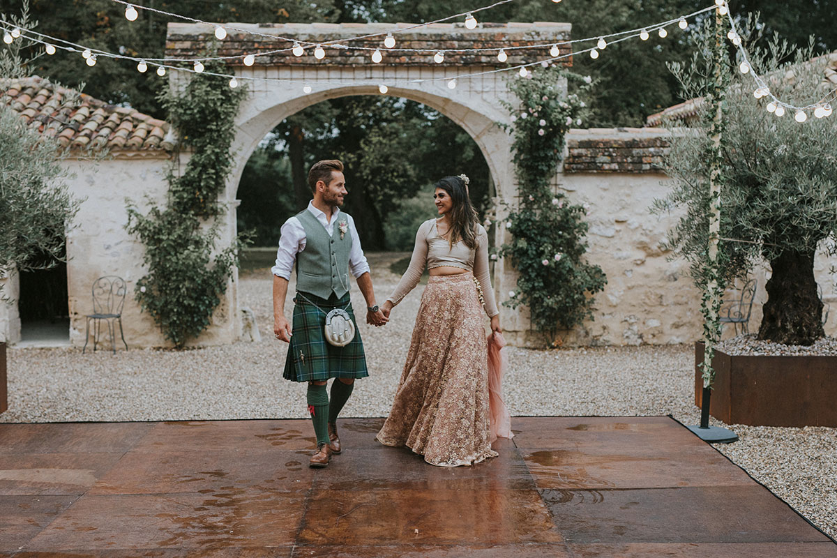 bride and groom holding hands and walking amid greenery and festoon lighting