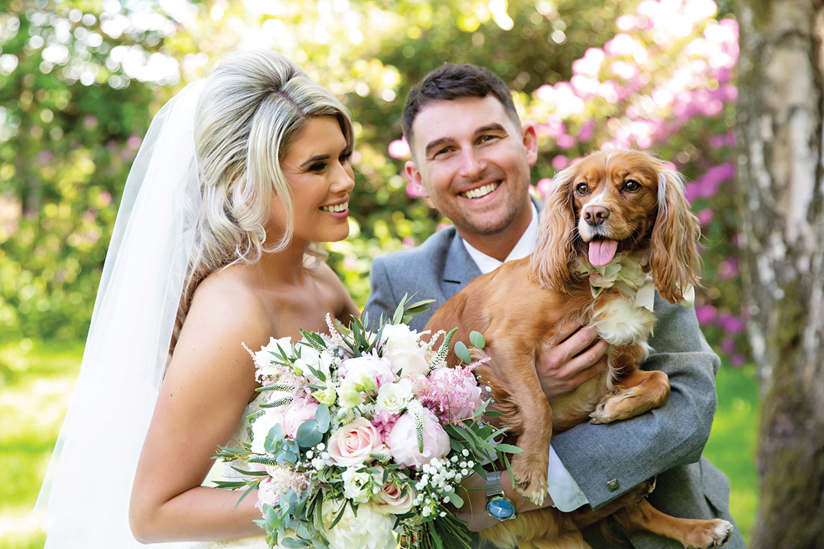 smiling bride and groom with King Charles Spaniel dog on wedding day