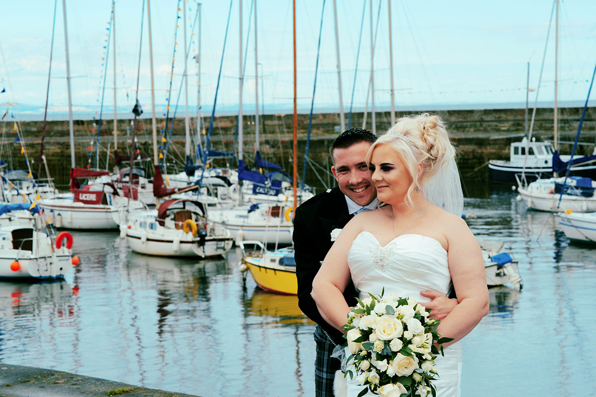 groom hugging bride from behind with boats and harbour in background