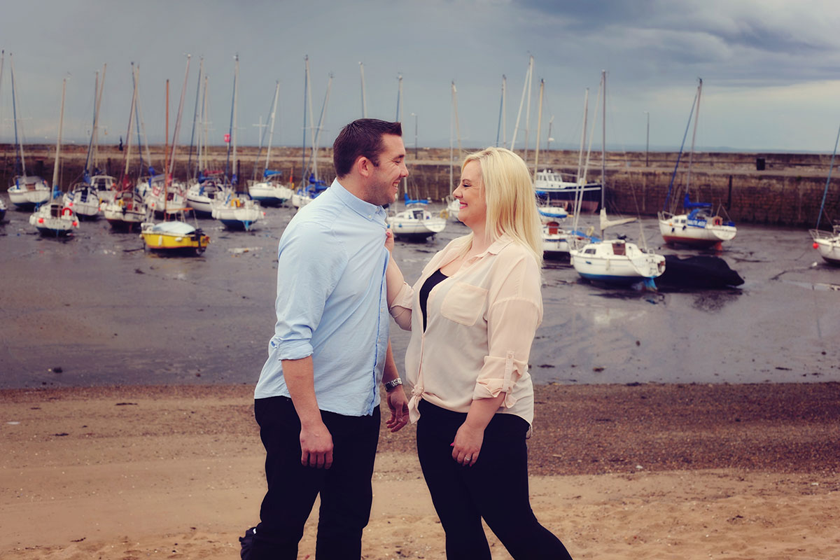man and woman looking at each other with boats and harbour in background