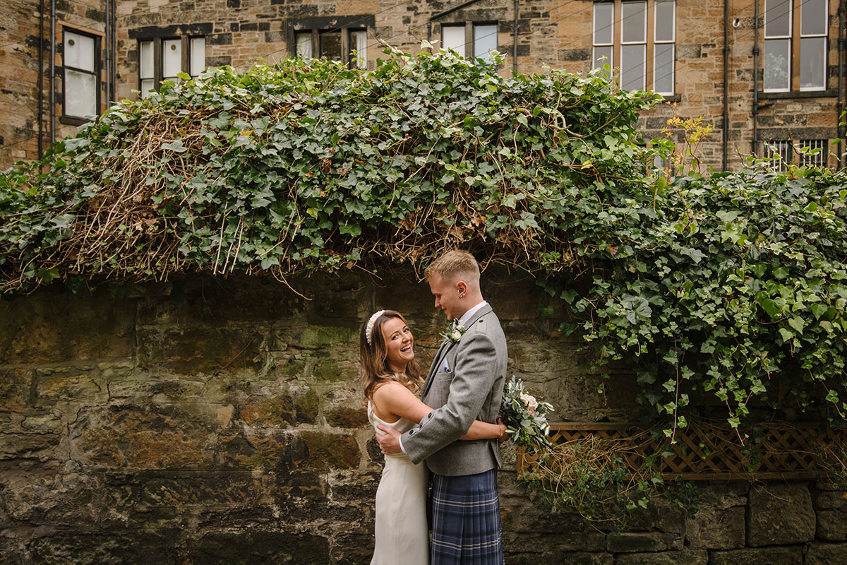 bride and groom standing by wall and hedge in Glasgow