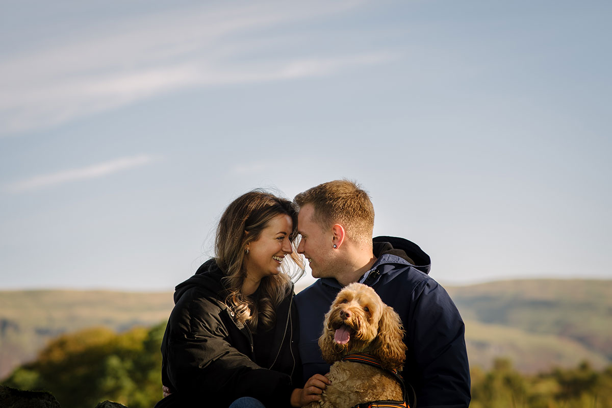 man and woman pictured outside in countryside landscape with heads together and happy pet dog