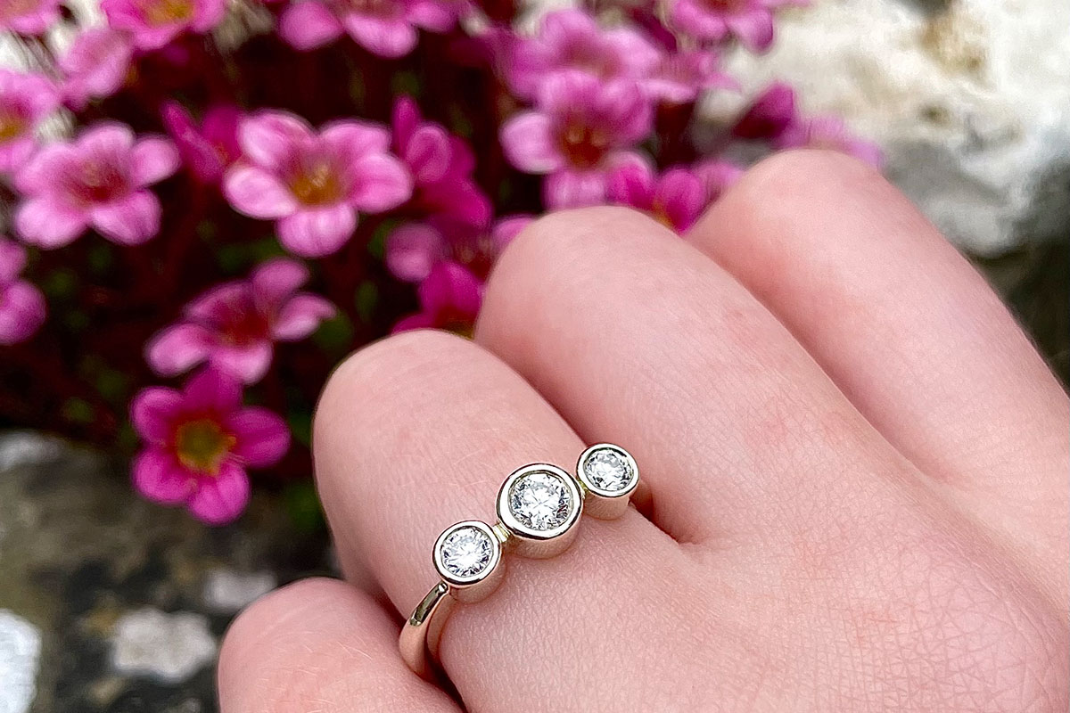 ladies' hand wearing a three-stone platinum engagement ring by Sheila Fleet with pink flowers in backgroud