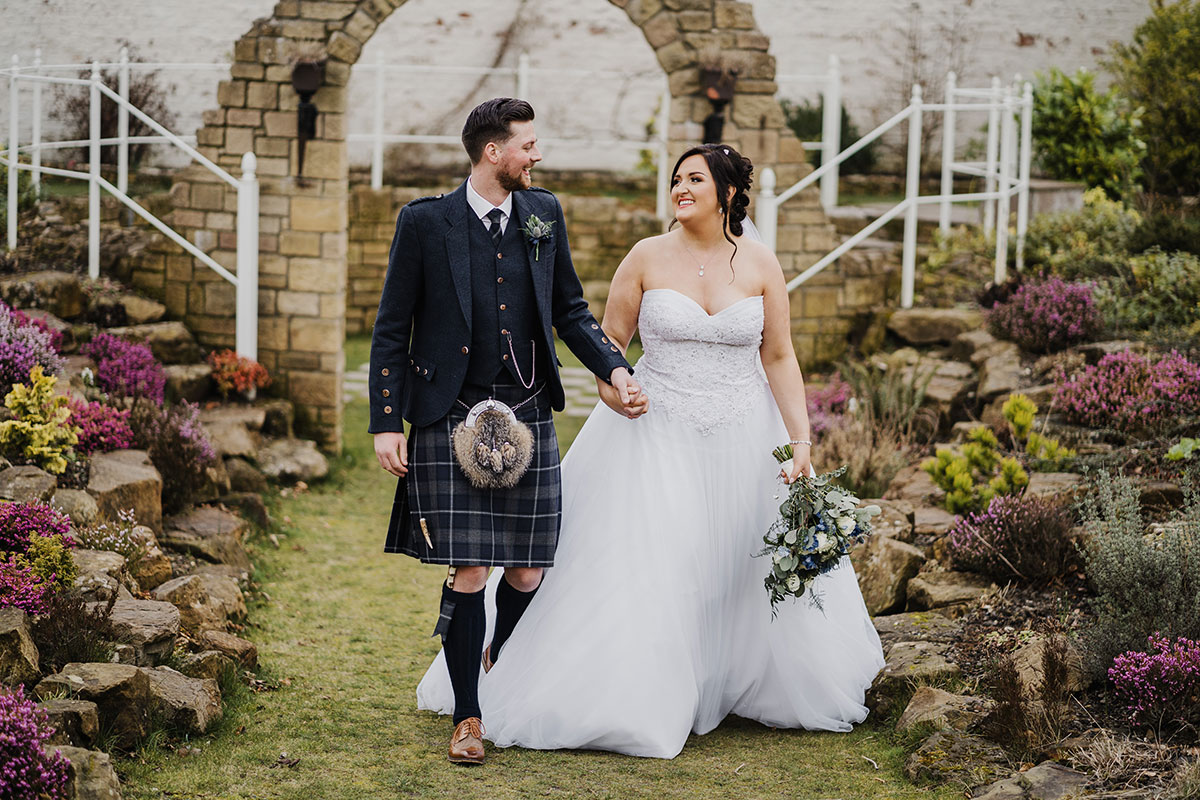 bride and groom holding hands walking through pretty garden in Scotland