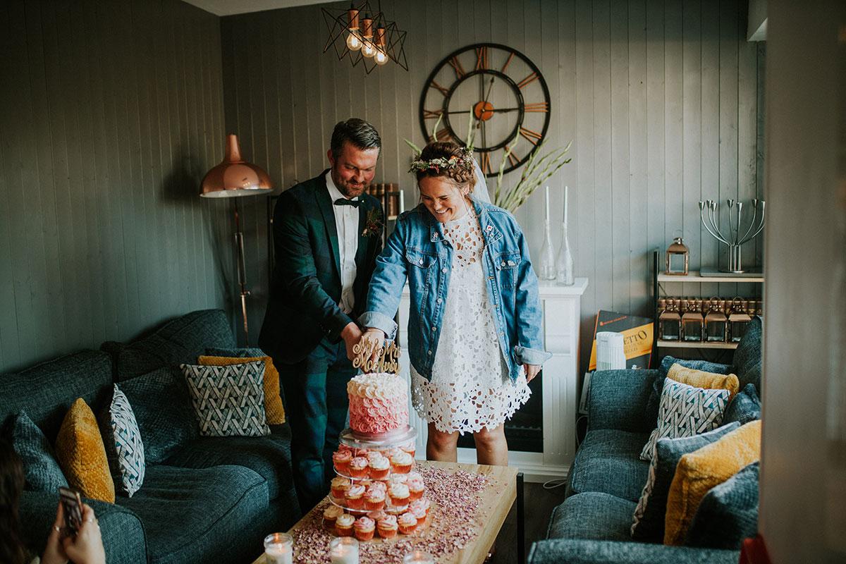 bride wearing denim jacket and groom wearing ASOS black watch suit cutting pink wedding cake at Jacob's Place in Edinburgh