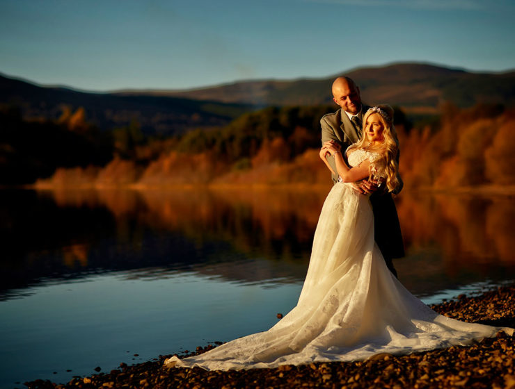 bride and groom basking in golden sunshine on the shore of Loch Insh in near Aviemore
