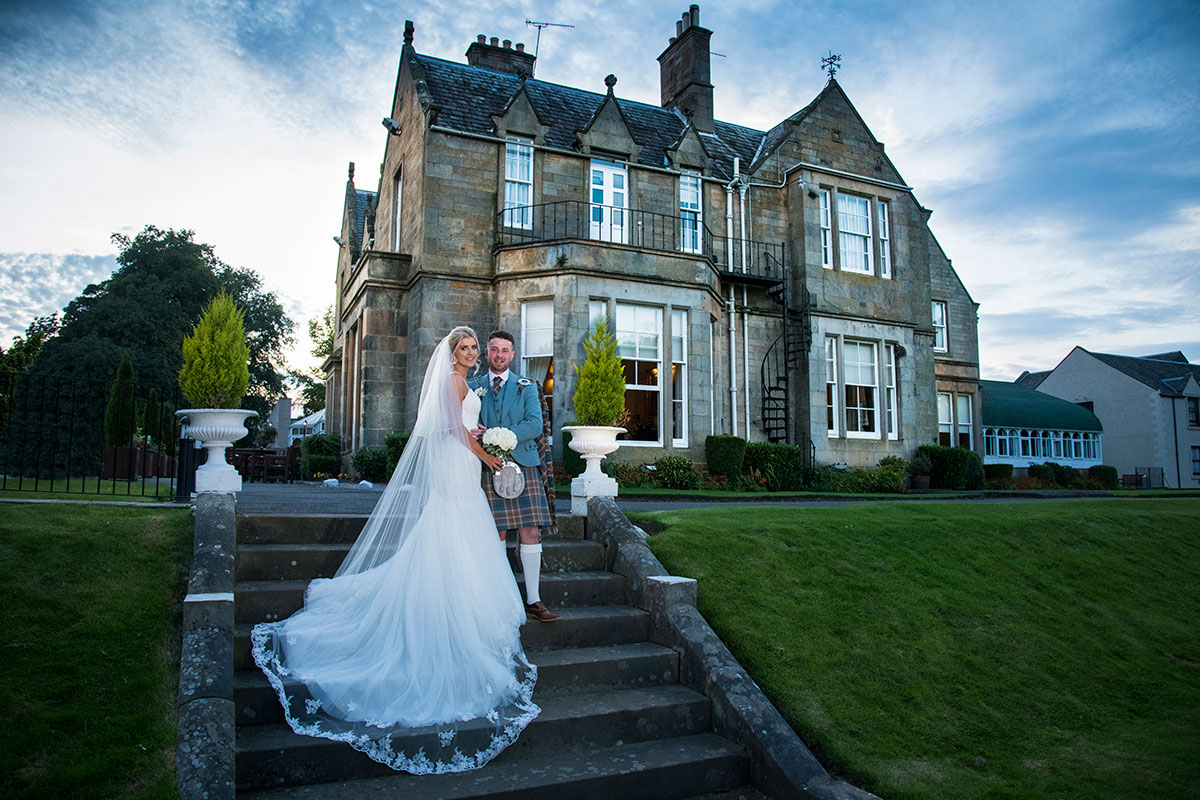 bride and groom standing on stairs in garden of Norton House Hotel near Edinburgh