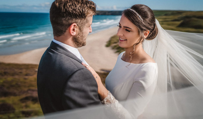 waist up image of bride and groom facing each other with a beach in the Isle of Lewis in the background
