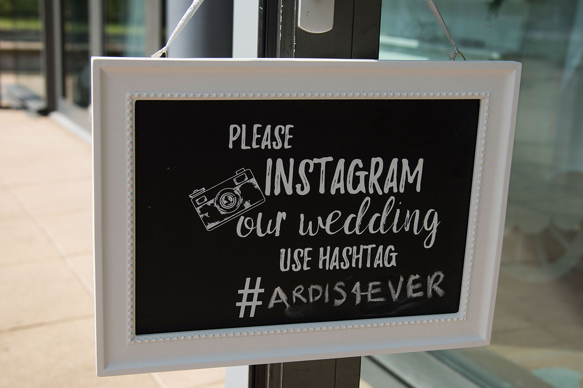 a black and white wedding sign encouraging wedding guests to Instagram their wedding using a hashtag