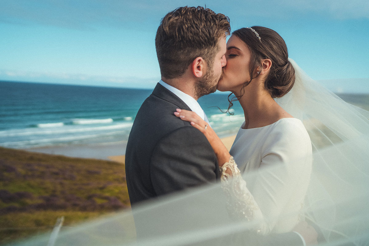 bride and groom kissing with a beach on the Isle of Lewis in the background