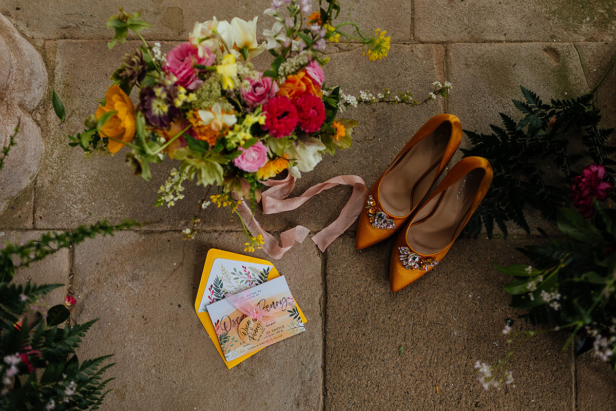 flat lay image of yellow shoes, wedding stationery by Two Tabbies and bridal bouquet by Briar Rose Design