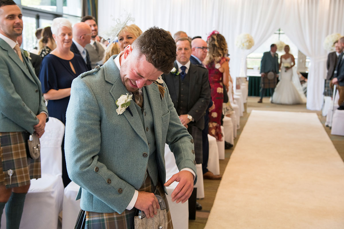 a groom crying at top of aisle with bride about to enter