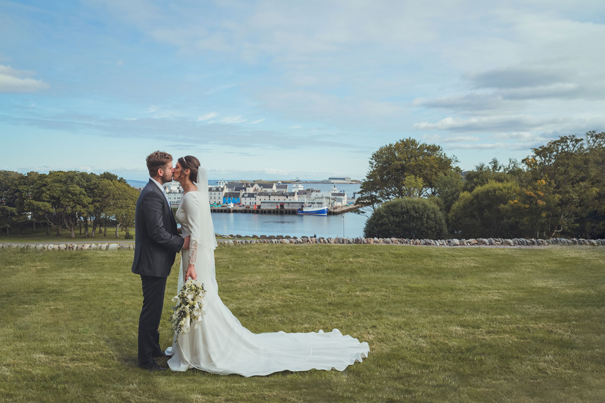 bride and groom kissing standing on grass with Stornoway in background