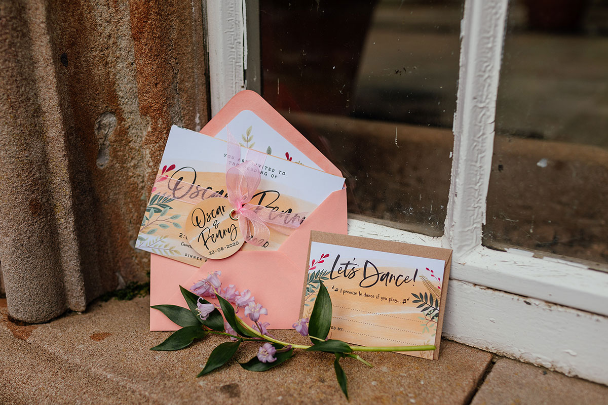 wedding stationery by Two Tabbies photographed against a white window frame and stone ledge