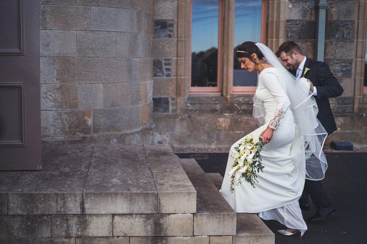 bride walking up steps with groom outside Lews Castle in Lewis