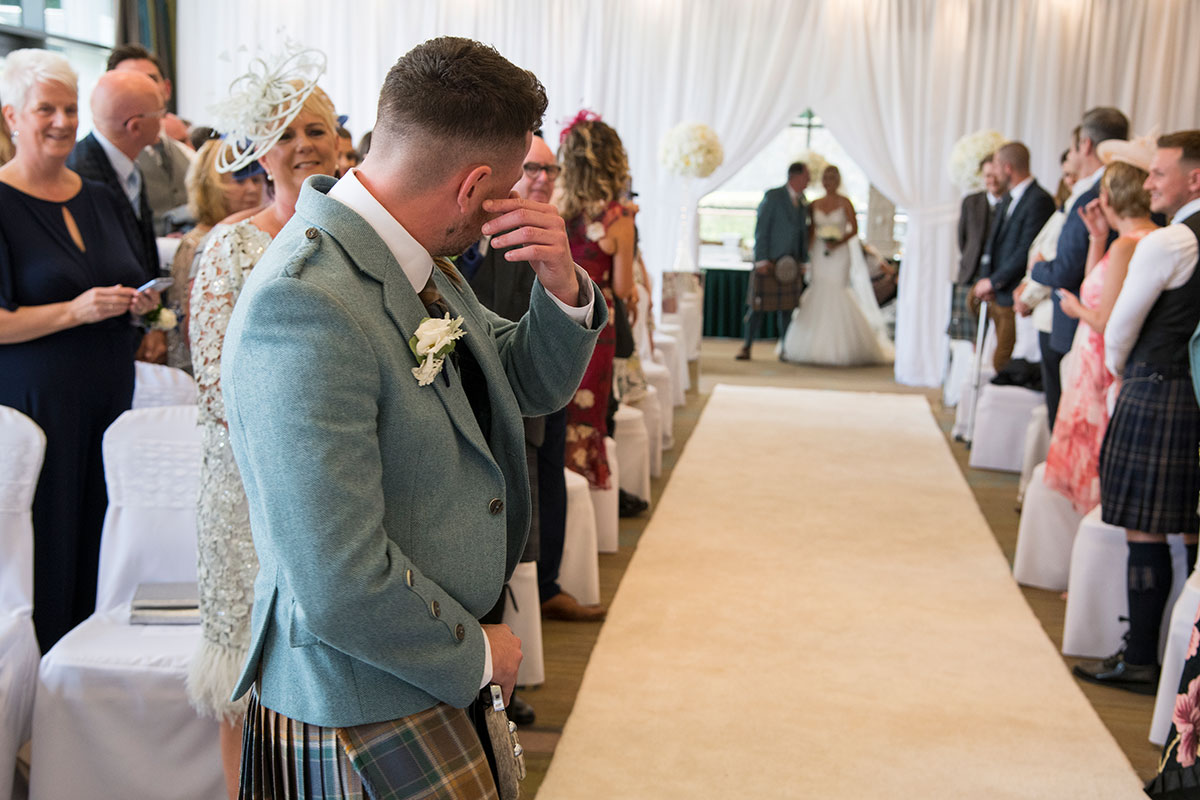 a groom wiping away his tears as the bride is about to walk down the aisle on the arm of her dad