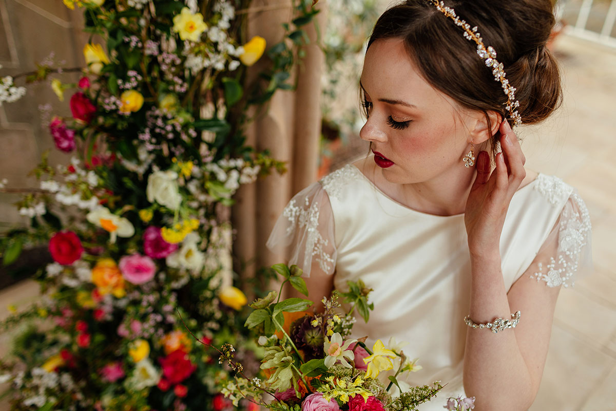 bride wearing jewellery by Susan Dick and wedding dress by Flossy and Dossy surrounded by colourful flowers by Briar Rose Design