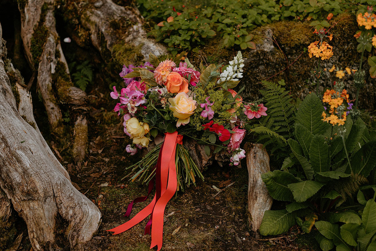 colourful summer wedding bouquet tied with coral ribbon against tree trunk by Adelaide's Secret Garden