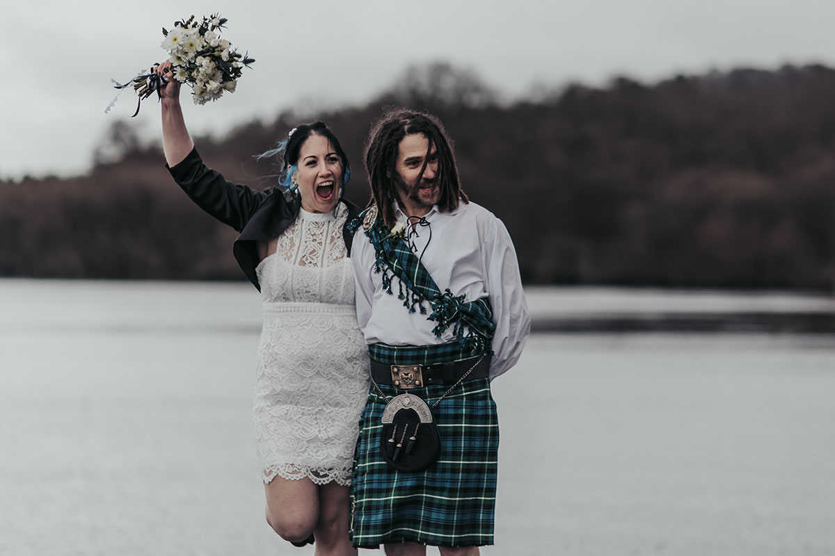 elated bride holding bouquet in air with groom wearing tartan fly plaid with Loch Lomond in background