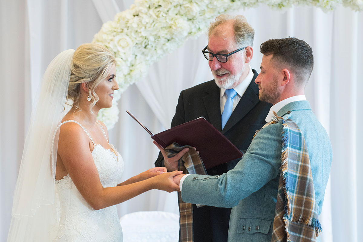 a bride and groom holding hands looking at each other while a male celebrant performs the ceremony