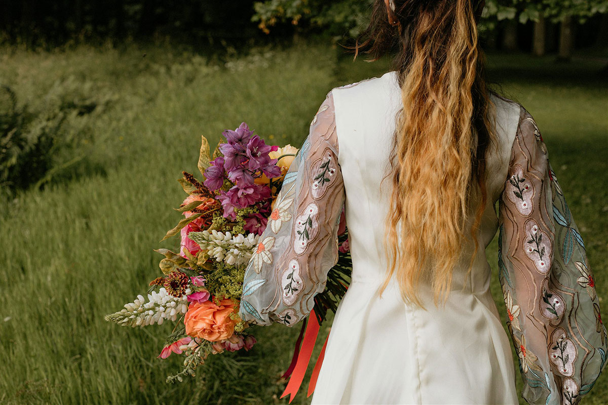 back of bride walking through grassy field wearing floral-sleeved dress by Rowan Joy and carrying bouquet by Adelaide's Secret Garden