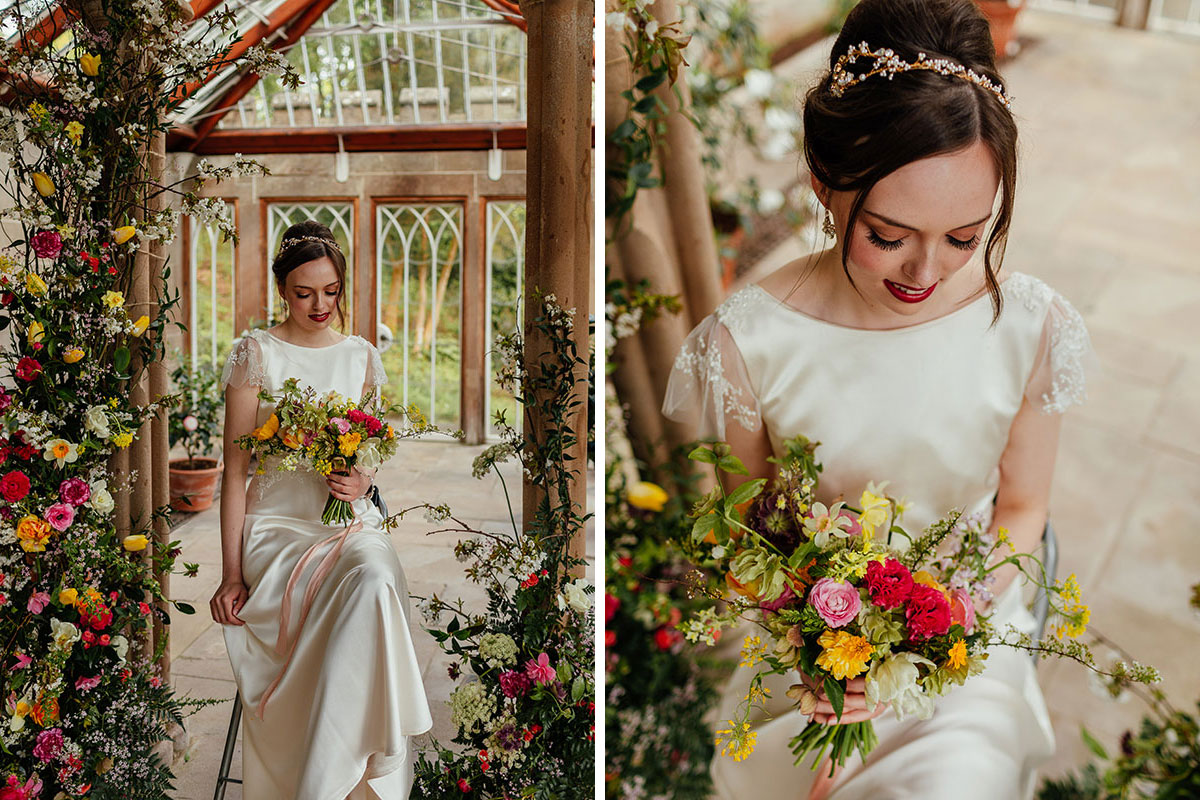 bride wearing an ivory dress with lace cap sleeves looking at a colourful wedding bouquet by Briar Rose Design