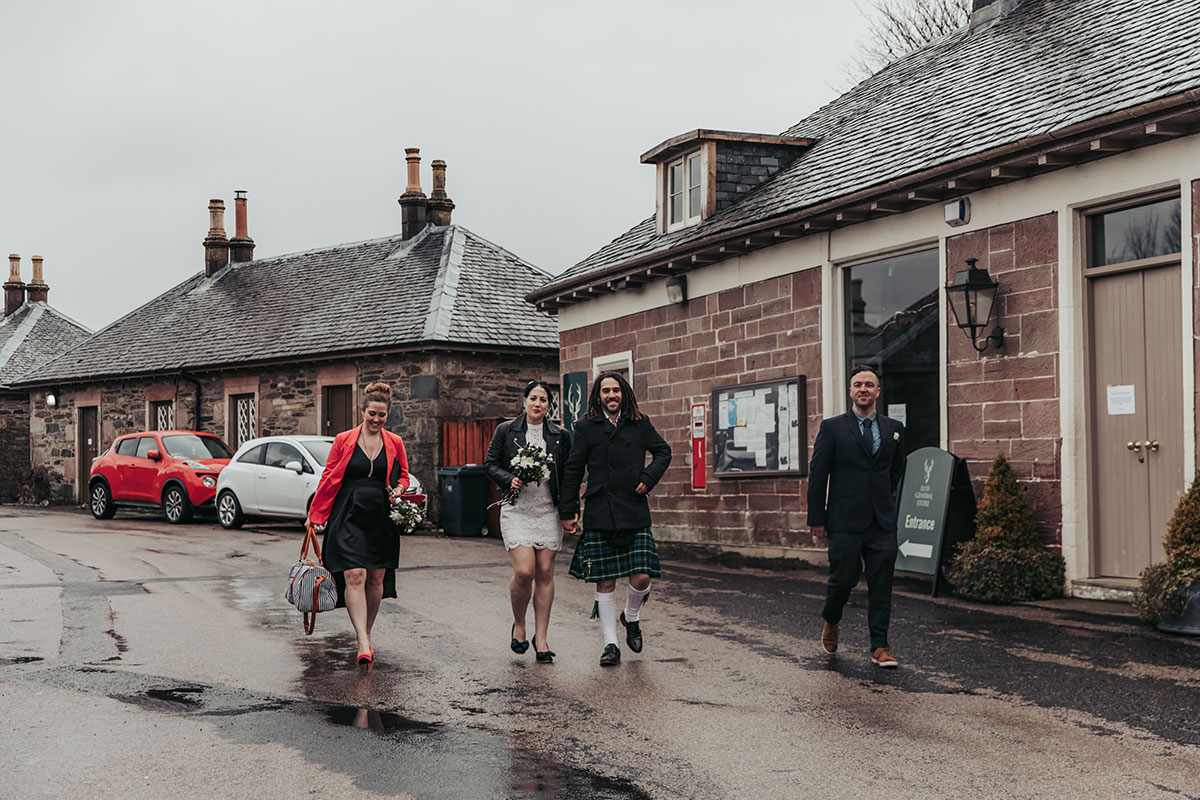 four people walking through the village of Luss at Loch Lomond