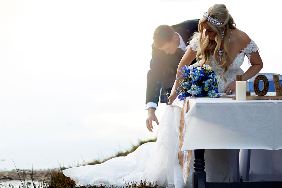 groom helping bride fix skirt when about to sit down at a table at a wedding outside