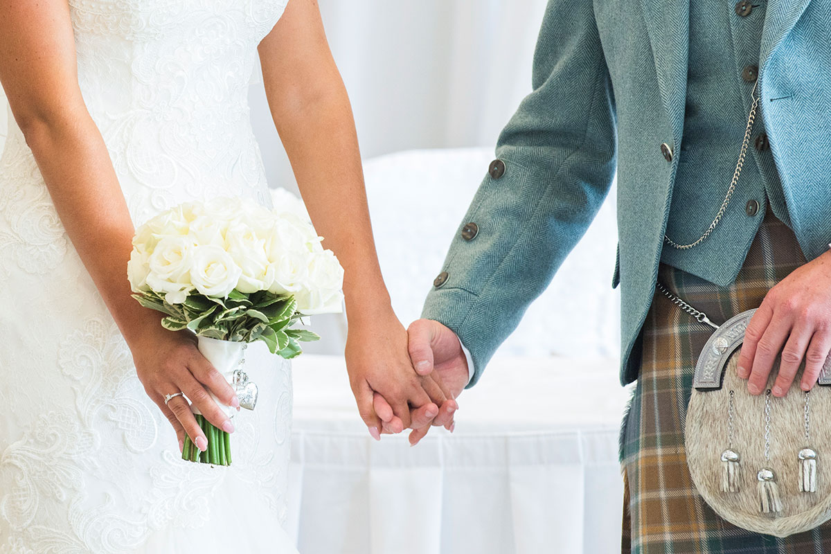 a torso crop image of bride and groom holding hands at a Scottish wedding