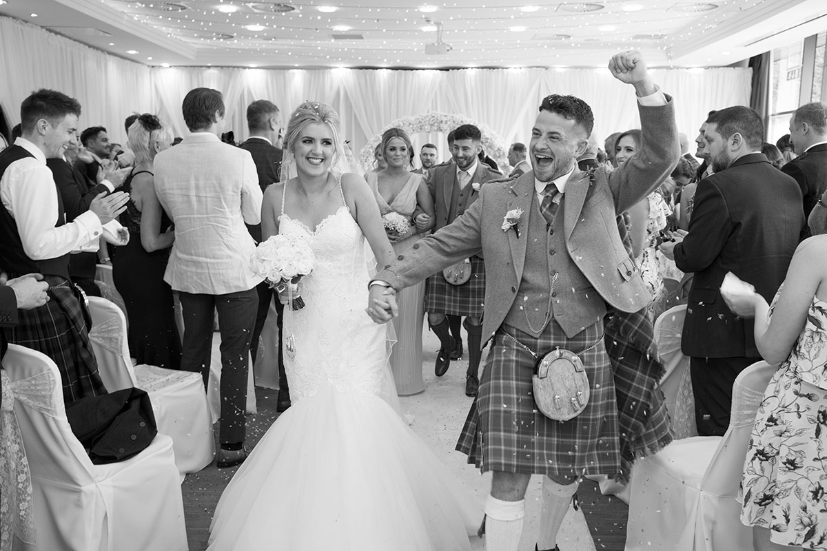 black and white image of bride and a cheering groom walking back up the aisle after their ceremony at Norton House Hotel