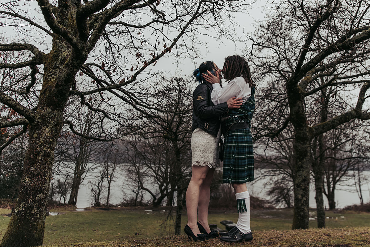 bride wearing short lace dress kissing dreadlocked groom on the banks of Loch Lomond with trees in background