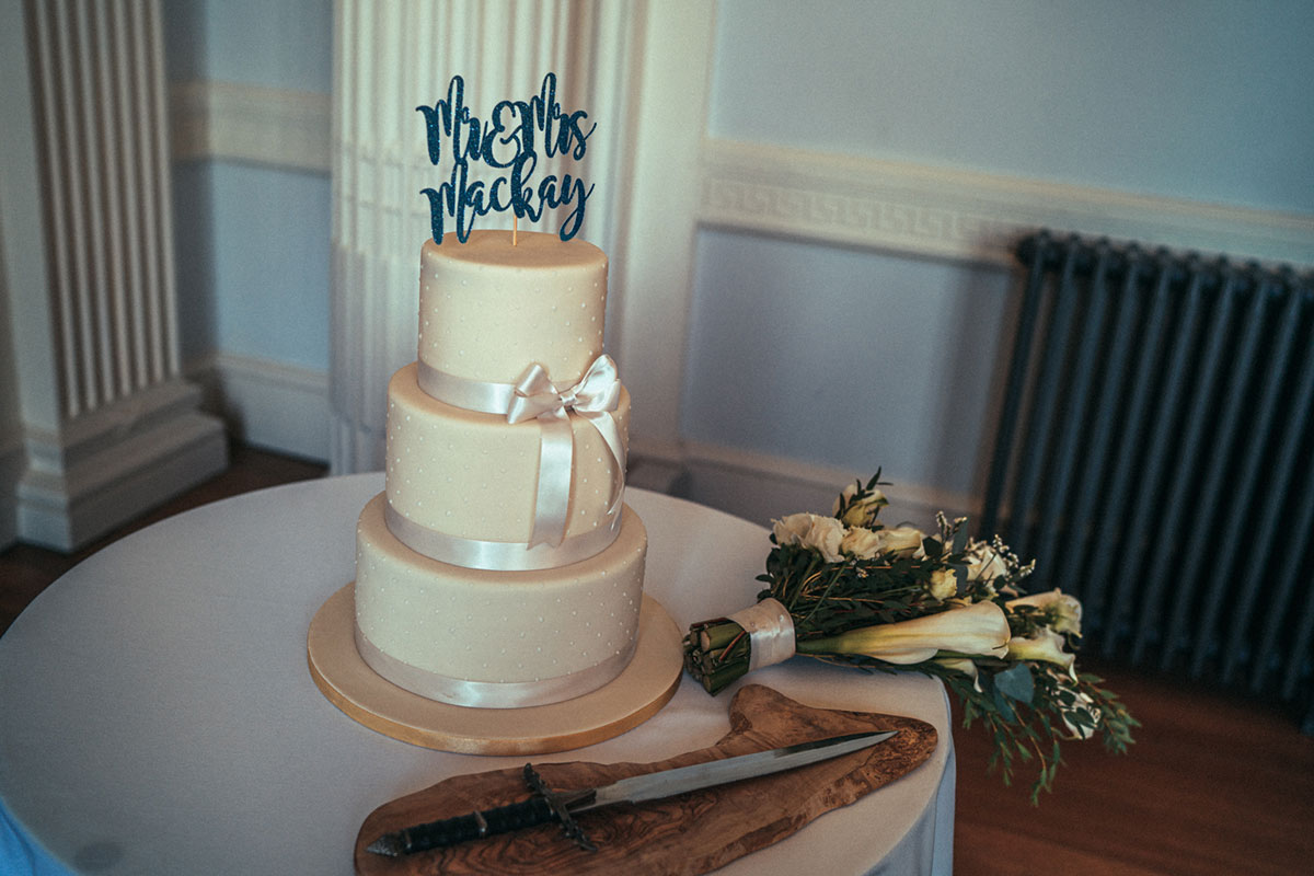 white three tier wedding cake with iced dots and white ribbon and blue glitter cake topper sitting on a table