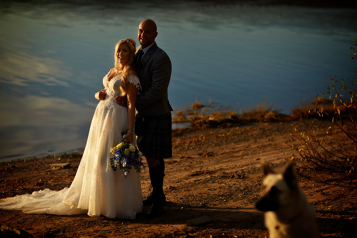bride and groom basking in the sunshine at Loch Insh with blurred out dog in foreground