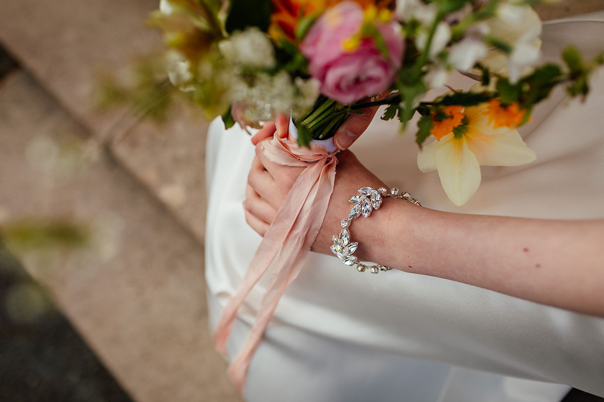 bride wearing crystal bracelet by Susan Dick Jewellery and holding colourful bouquet of flowers