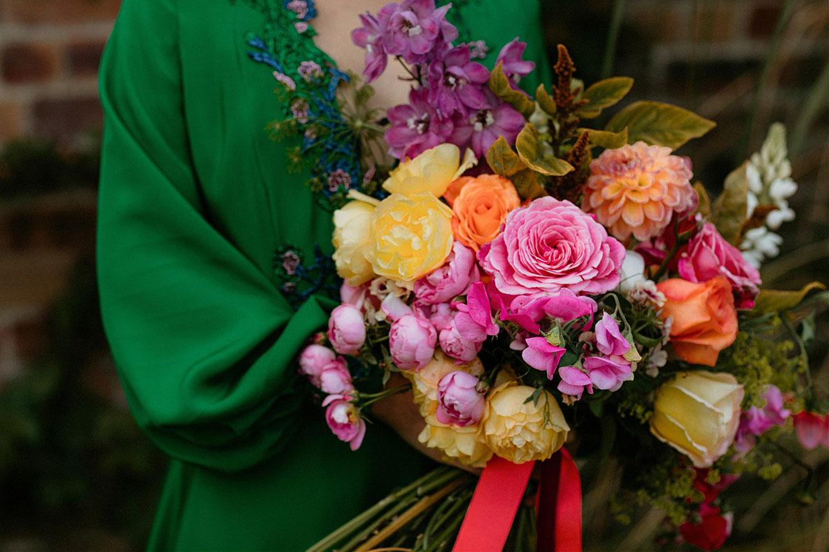 bride wearing green Rowan Joy wedding dress holding pink yellow and orange bridal bouquet by Adelaide's Secret Garden