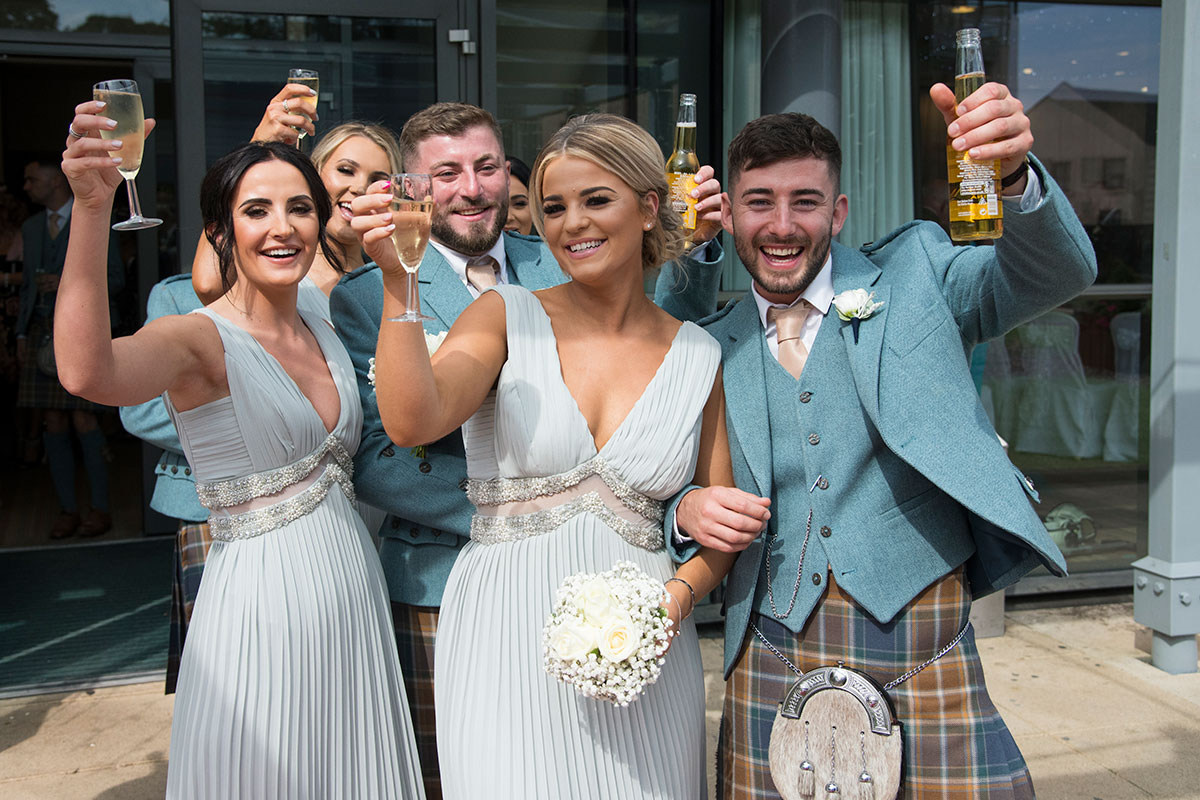 bridesmaids and ushers raising glasses of prosecco and bottles of beer at a wedding at Norton House Hotel