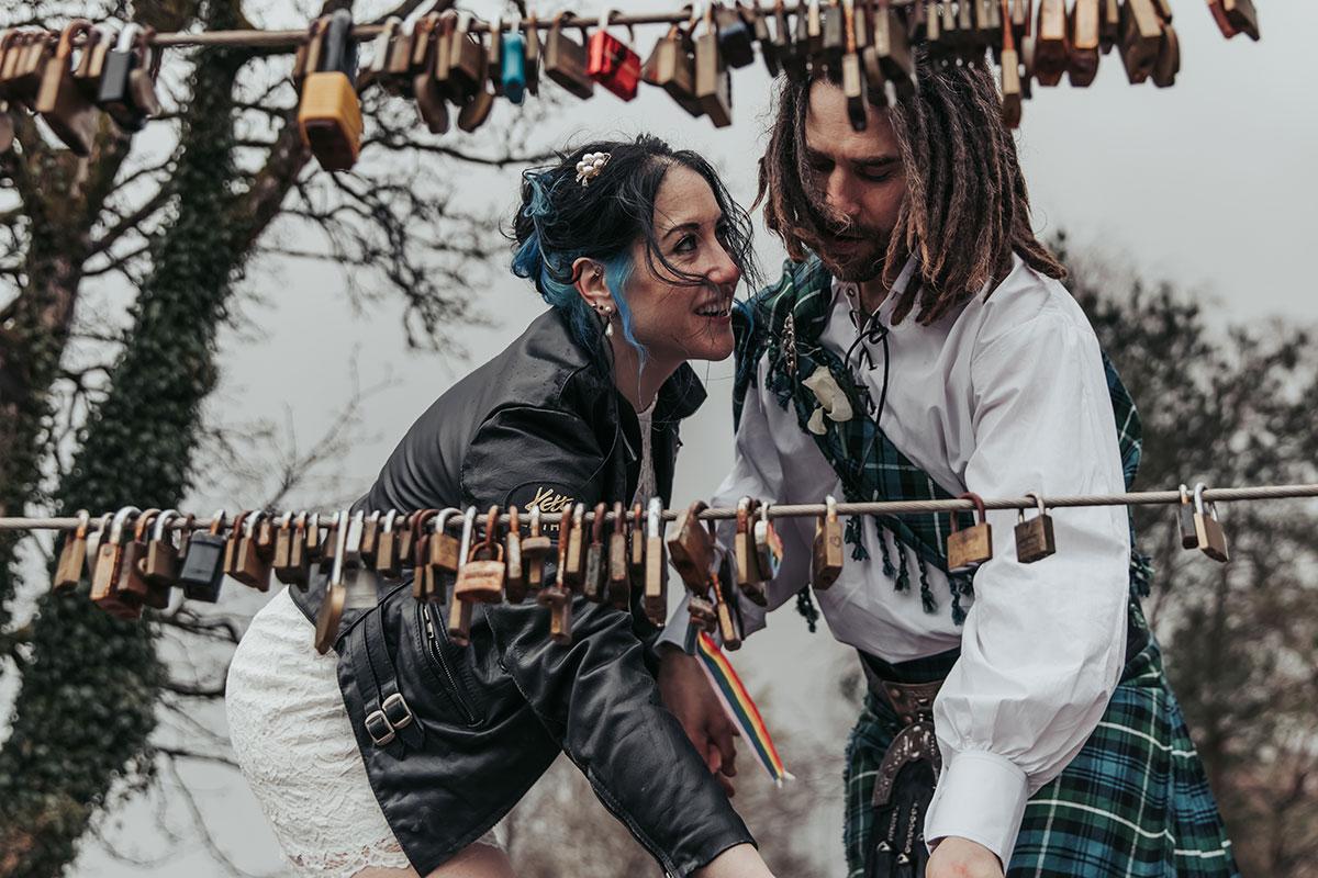 bride and groom fastening padlock on wire at Loch Lomond