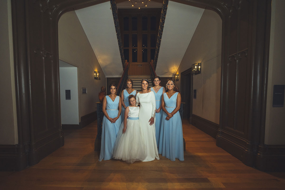 bride, four bridesmaids wearing blue and flower girl posing for a photo on the staircase at Lews Castle