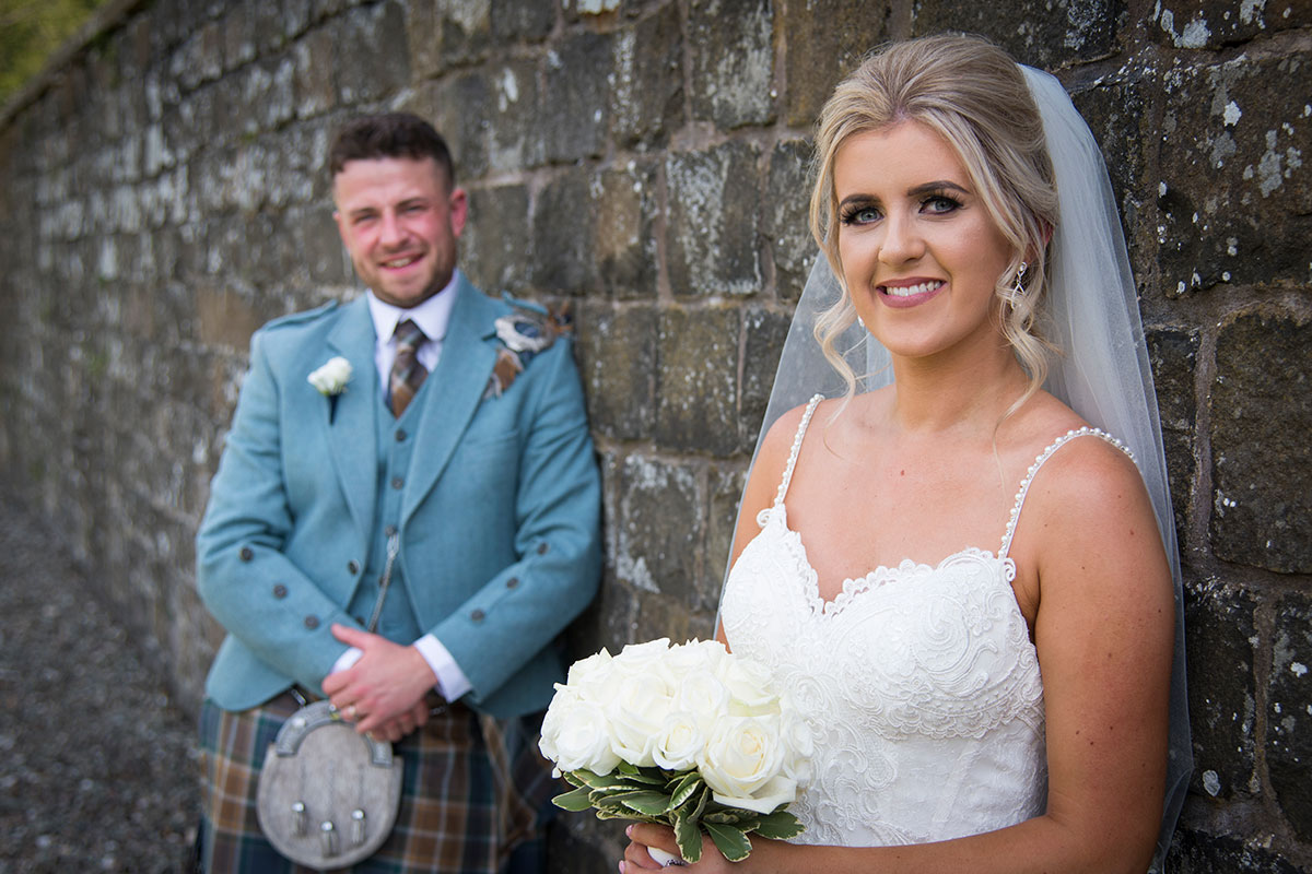smiling bride in foreground and groom in background posing against concrete wall