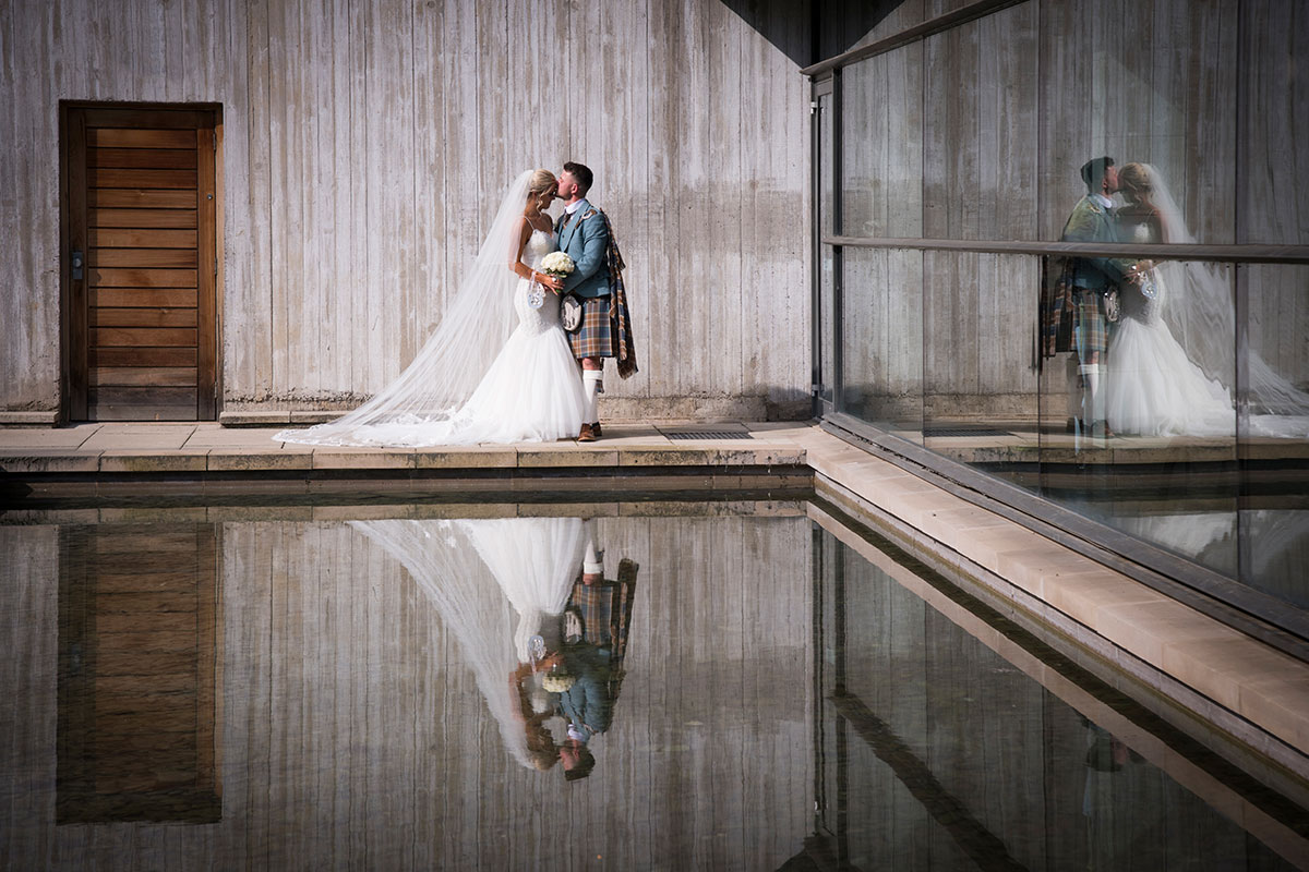 bride and groom kissing beside sunken gardens at Norton House Hotel with reflection in water