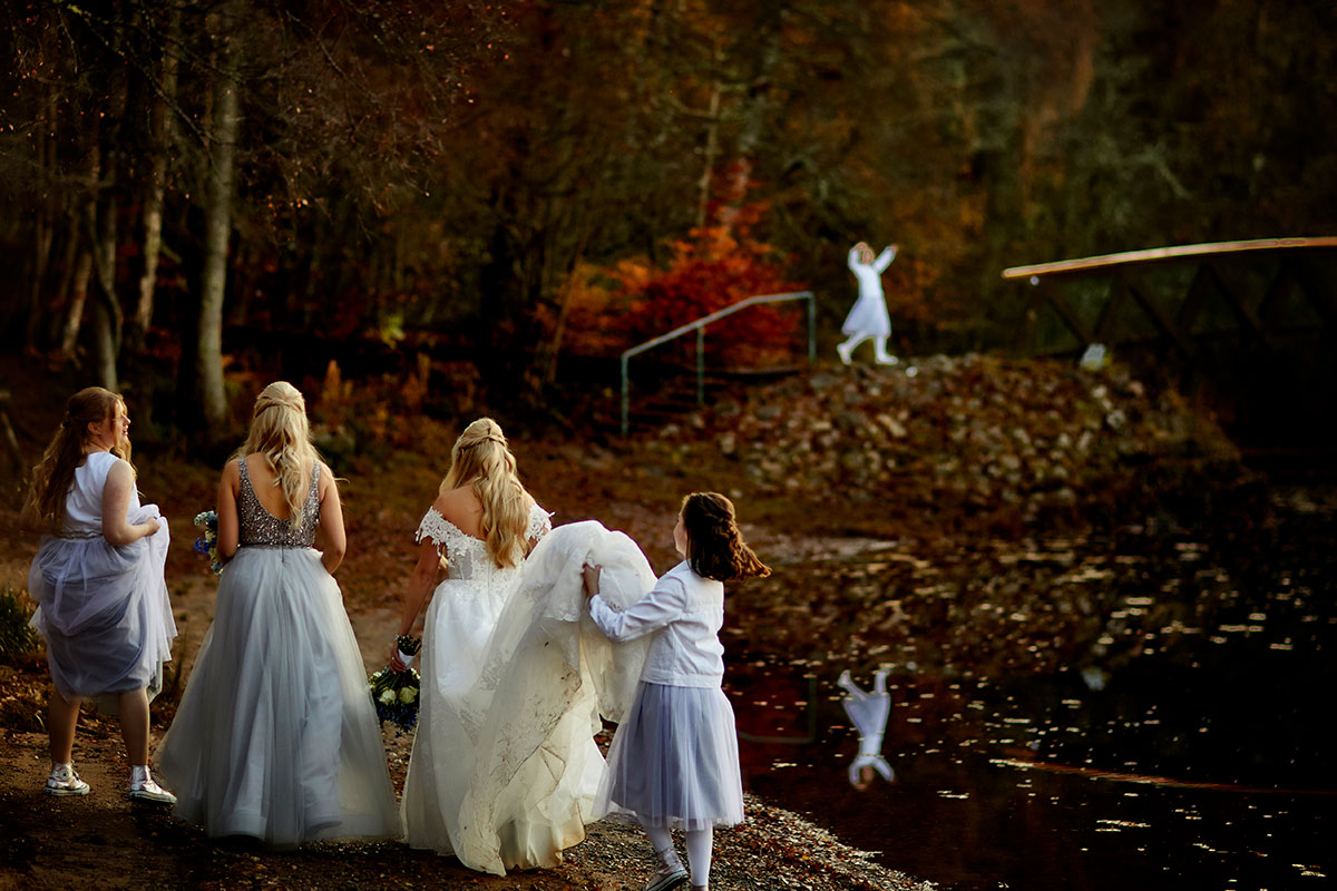 bride walking along the shore of Loch Insh with bridesmaids and young bridesmaid carrying her dress train