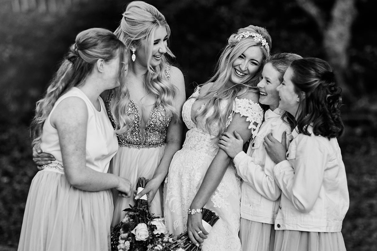 black and white image of bride and four bridesmaids laughing and looking at one another