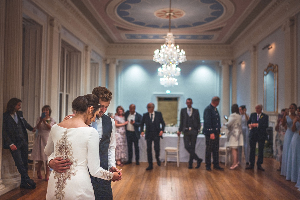 bride and groom having a first dance at Lews Castle while guests watch on fron edge of dancefloor