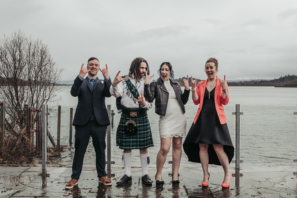 bride and groom with two wedding witnesses making rock signs with hands on the shores of Loch Lomond