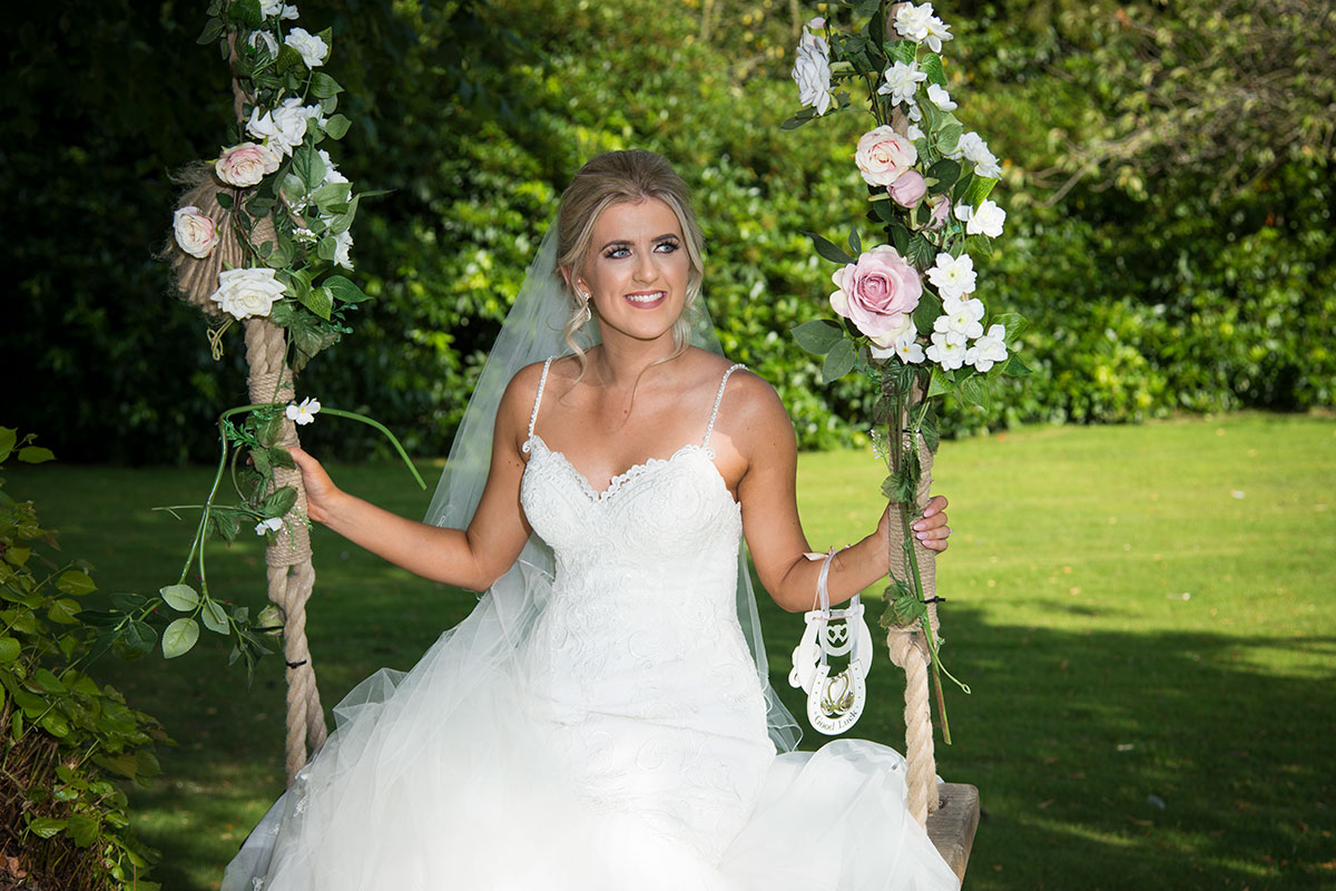 bride sitting on wooden swing decorated with flowers at Norton House Hotel