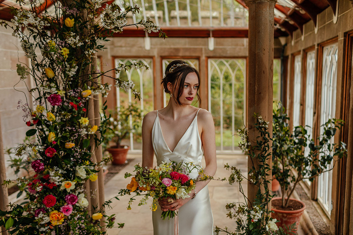 bride wearing camisole-style ivory slip wedding dress in the Camellia House at Culzean Castle