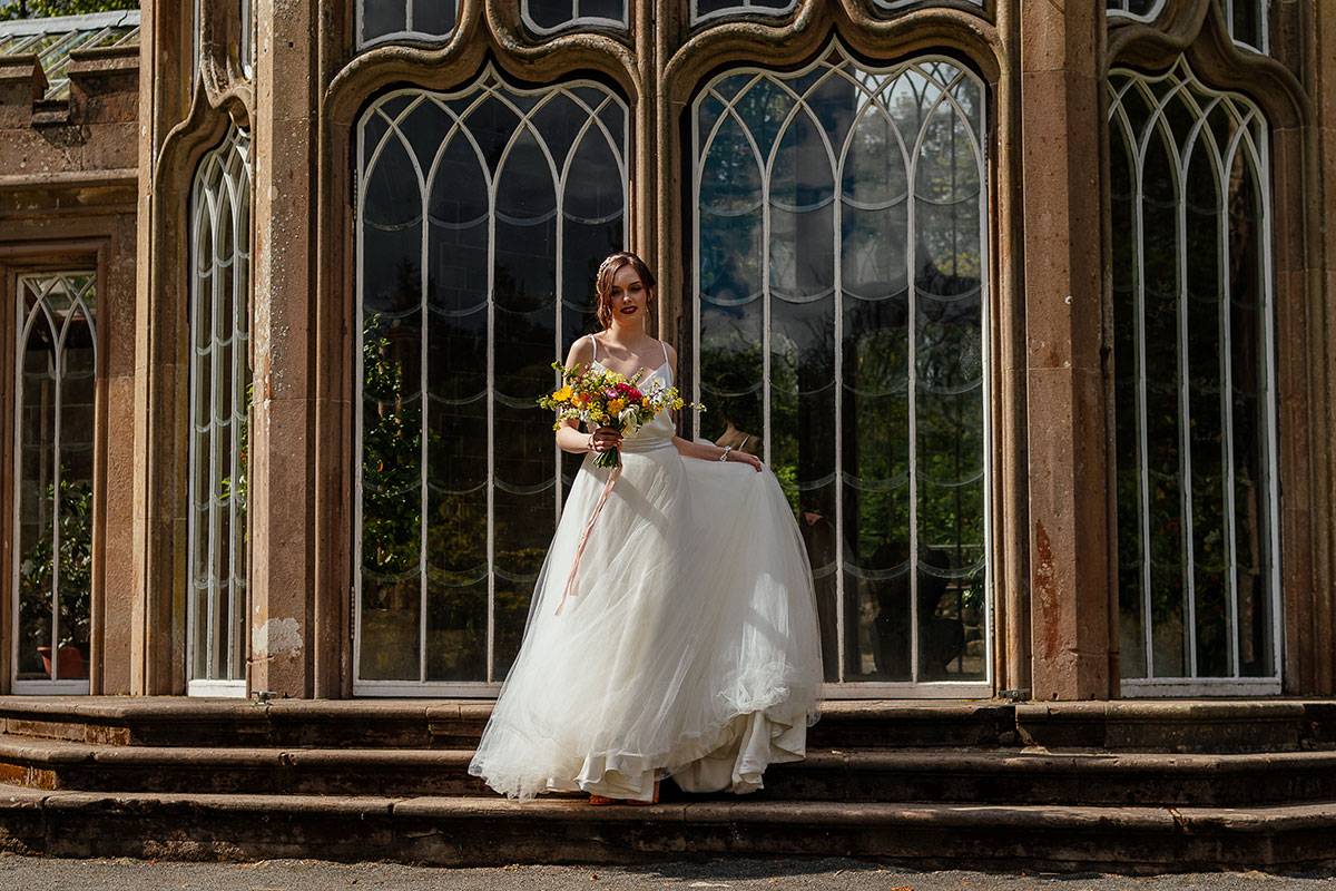 a bride walking down the steps outside the Camellia House at Culzean Castle wearing a Flossy and Dossy wedding dress