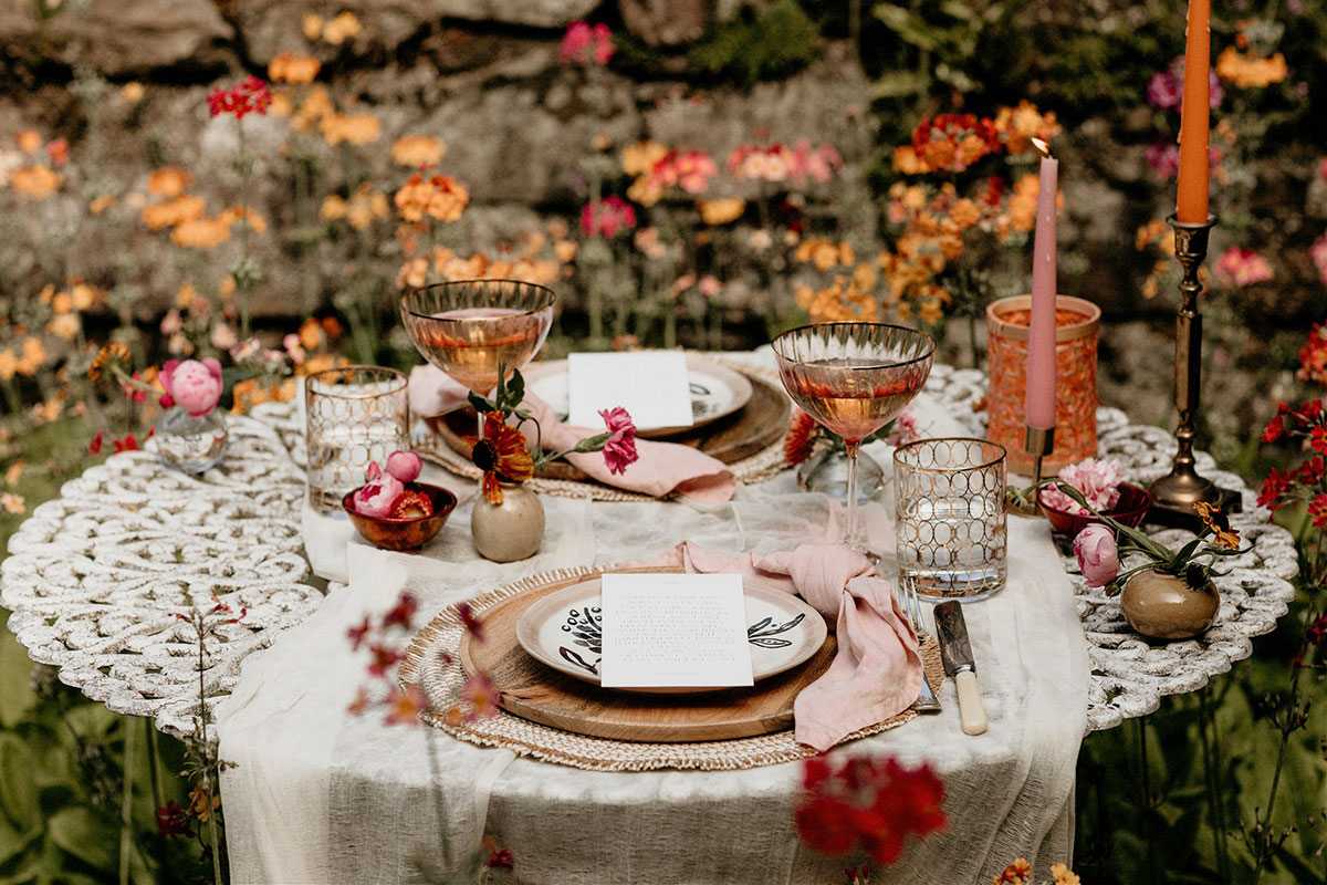 alternative colourful floral wedding styled table in summer woodland with glassware candles and plates