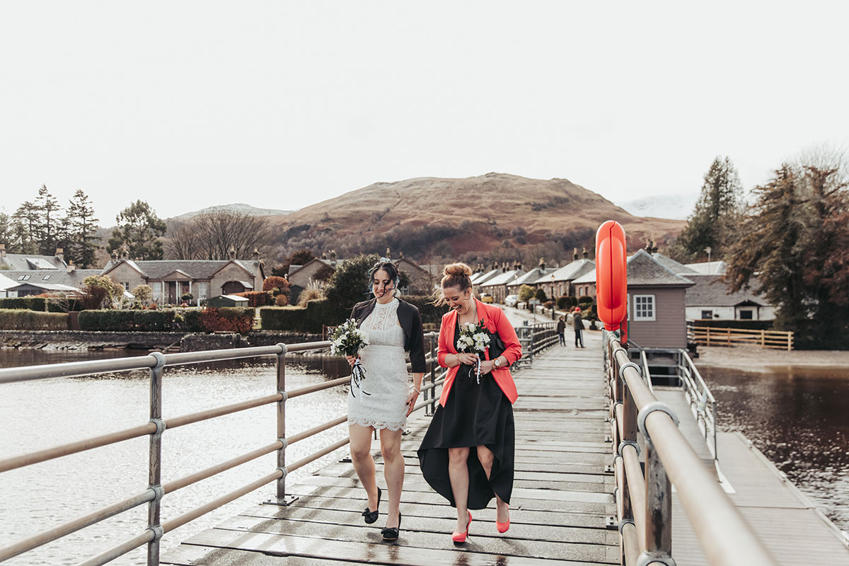 bride wearing short lace dress and black bolero walking with a person wearing a skirt on the pier at Luss at Loch Lomond