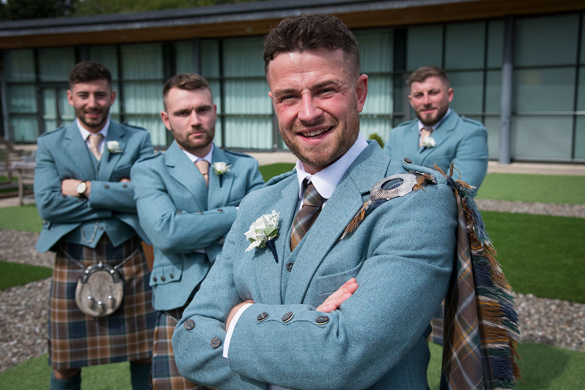 groom and three ushers with arms folded wearing teal tweed jackets and brown and blue tartan kilts
